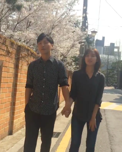 """Jin Goo and Kim Ji Won Hold Hands in Video Encouraging Fans to Watch """"Descendants of the Sun"""" Live"""