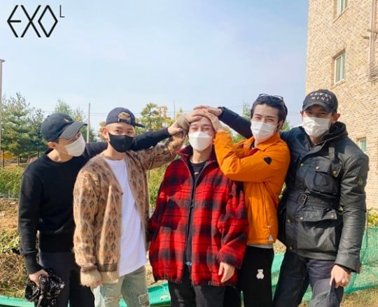 Member EXO menutupi kepala Chen EXO yang rambutnya sudah dipotong guna dinas wajib militer.