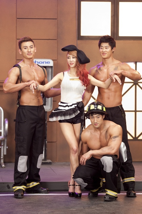 G.NA Gets Surrounded by Topless Firefighters in New Teaser Video